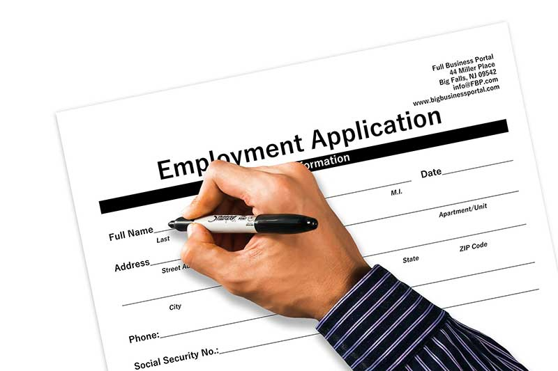 Image of a hand with a marker filling out a job application during their job search