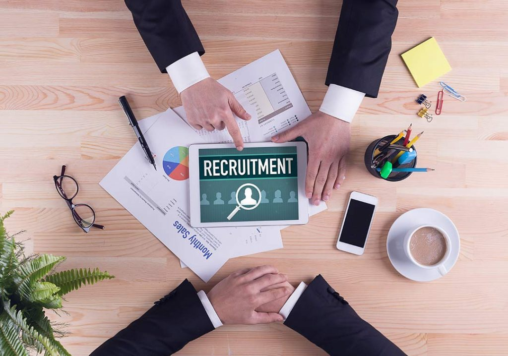 "Image of a table with the word ""Recruitment"" on a table. Two people are at each end and you only see their arms. They appear to be wearing a suit."
